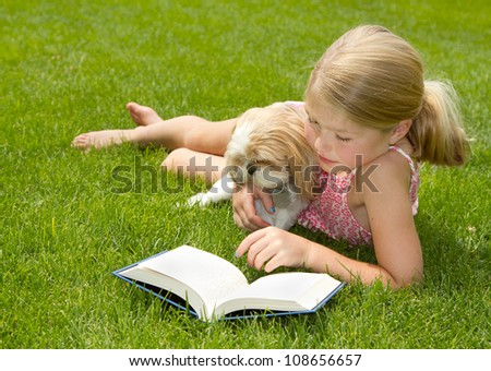 Girl reading with pet dog outdoors in the grass