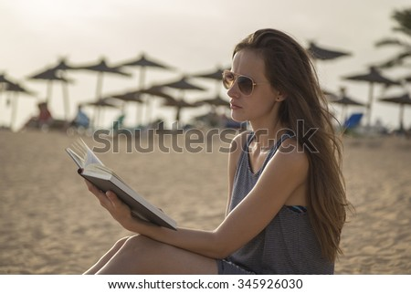 girl reads a book at the beach, relax in background beach umbrellas - stock photo