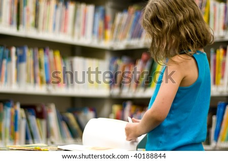 girl reads a book at the library with copyspace