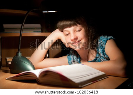 Girl reads a book late at night - stock photo
