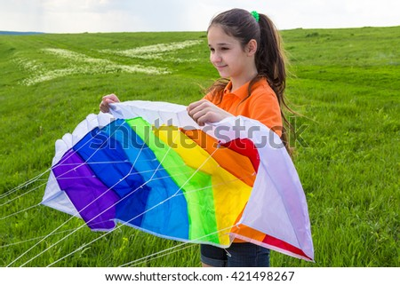 Girl ready to runs a colorful kite on the green lawn