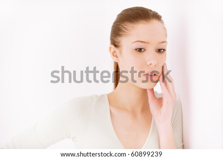 Girl reflects on life, against light wall. - stock photo