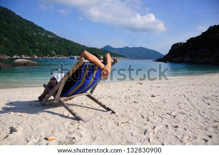 Girl relax on beach chairs on tropical white sand beach in koh tao, thailand - stock photo