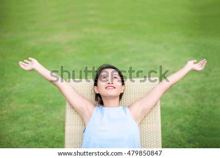 girl relax with arms wide open in green nature