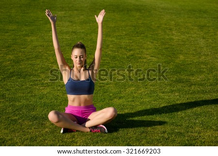 Girl relaxes on a green lawn. Girl meditates on the street. Yoga classes.