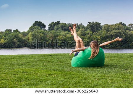 Girl relaxing in a bean bag chair on the green grass - stock photo