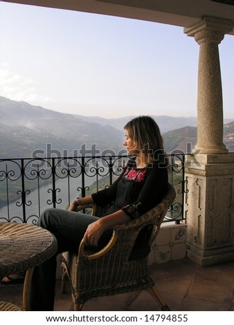 Girl relaxing in a luxurious balcony over the douro river, in the Oporto wine region, Portugal - stock photo