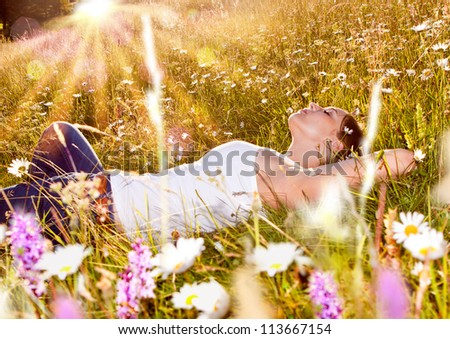 girl relaxing in a meadow in the sunset - stock photo