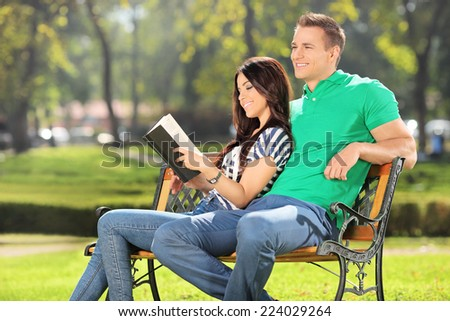 Girl relaxing in a park with her boyfriend seated on a bench  - stock photo