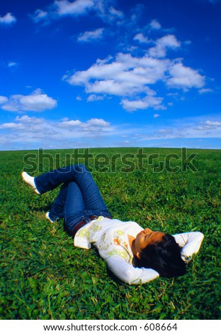Girl relaxing on a field of grass.