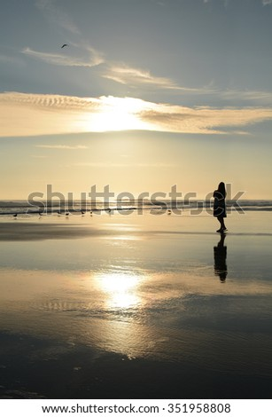 Girl relaxing on beautiful golden beach at sunrise, Daytona Beach, Florida. - stock photo