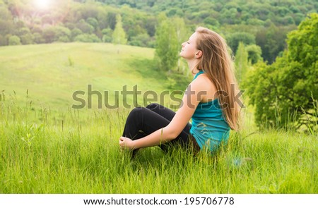 Girl relaxing on green grass. Young happy woman sitting on the hill. - stock photo