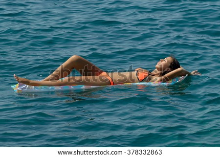 Girl relaxing on inflatable beach mattress in the sea