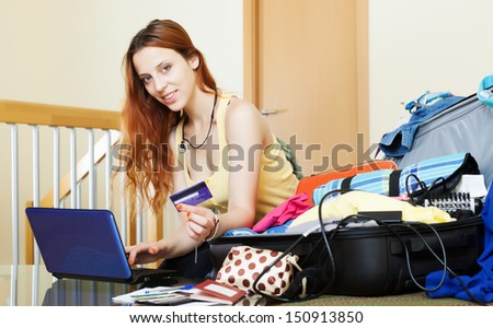 Girl reserving hotel online with laptop and credit card at home