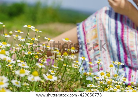 Girl resting and relaxing in a field of daisies - DOF