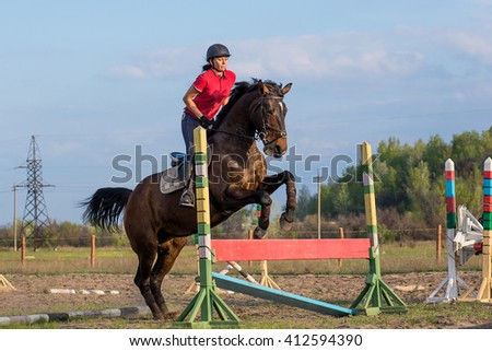 Girl rider on a horse jumping over a hurdle