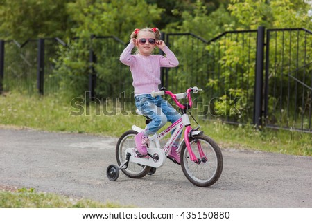 girl rides a bicycle on a warm summer track - stock photo