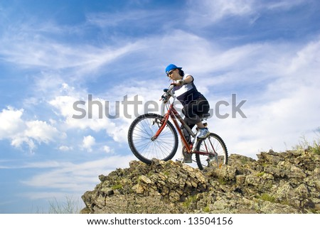 Girl rides a bike in mountains.