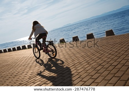 Girl rides a bike on the promenade by the sea at sunset. Focus on the pavement. On image superimposed filter Color Lookup. - stock photo