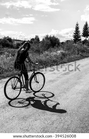 girl riding a bicycle on a road on a sunny summer day,  vacation in countryside, black and white - stock photo