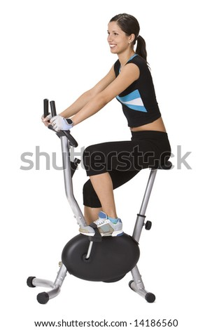 Girl riding a fitness bicycle against a white background.