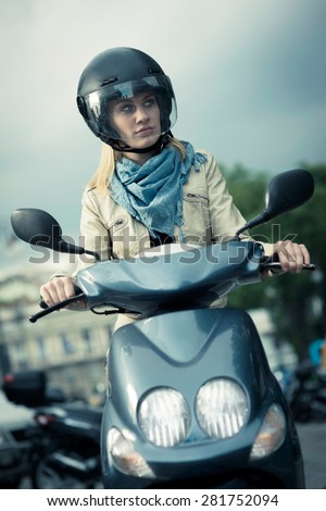 Girl riding motor scooter - stock photo