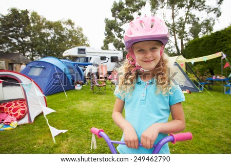 Girl Riding Scooter Whilst On Family Camping Holiday  - stock photo