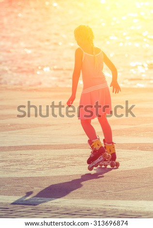Girl roller-skating in the city center when it is backlit. Sport composition - stock photo
