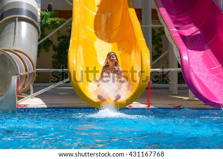 girl rolls down the water slides at the water park - stock photo