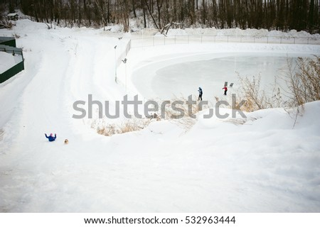 girl rolls from the hill in the snow with a dog