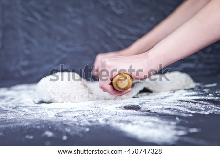 Girl rolls out the pizza dough with the rolling pin on black table - stock photo