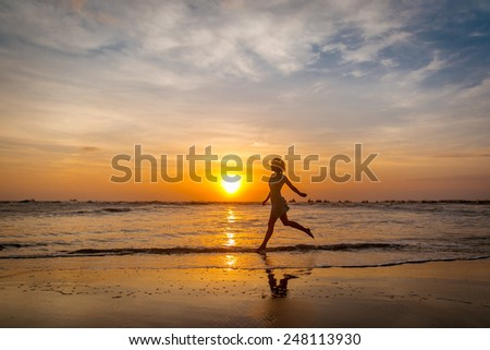 Girl running along the seacoast on the sunset