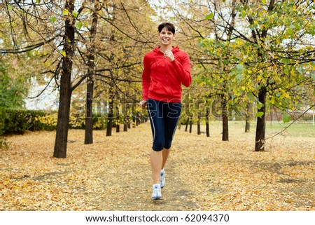 Girl running among autumn trees and smiling - stock photo