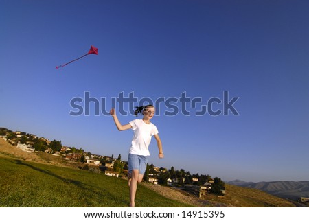Girl running and flying a kite in a park with blue sky