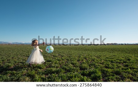 Girl running and playing with globe in farm field. - stock photo