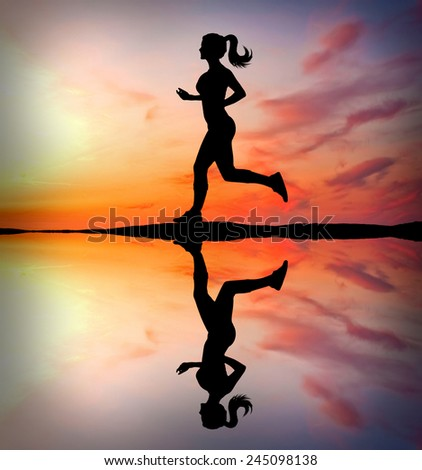 Girl running at sunset with reflection in water - stock photo