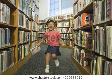 Girl running down aisle of library - stock photo