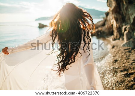 girl running dreamy with wind in hair and sunflare on beach sunset. defocus - stock photo