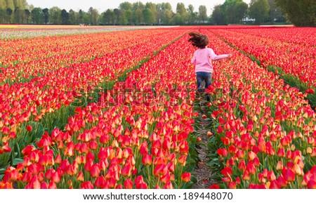 Girl running in a flower field - stock photo