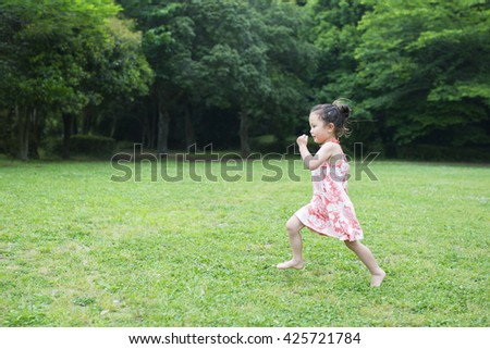Girl running in the grassland - stock photo