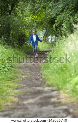 Girl running on a path in the woods