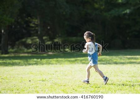 Girl running on lawn - stock photo