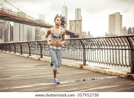 Girl running on the pier with New york skyline in the background - stock photo