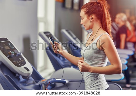 Girl running on the treadmill and listening to music at the gym, soft focus picture - stock photo