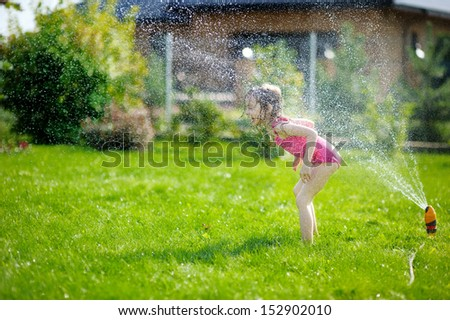 Girl running though a sprinkler in a backyard