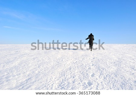 girl running through a snowy field - stock photo