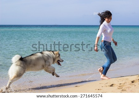 Girl running with her dog on beach