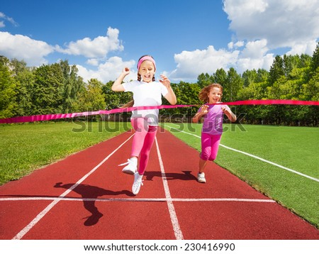 Girl runs and reaches ribbon excited to win the marathon and second girl runs behind - stock photo