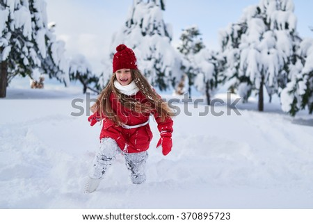 Girl runs and rejoices in a snowy park
