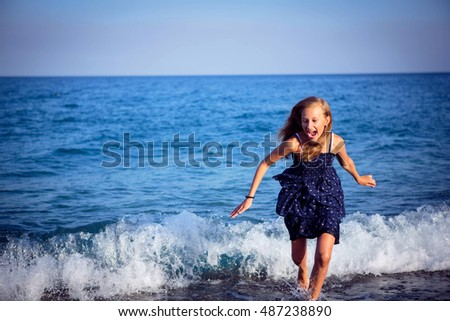 girl runs away from a wave